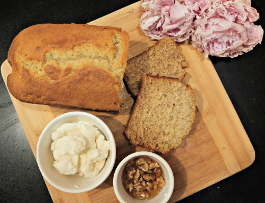 Banana bread loaf with slices next to a bowl of creme fraiche cheese and a bowl of honey infused walnuts